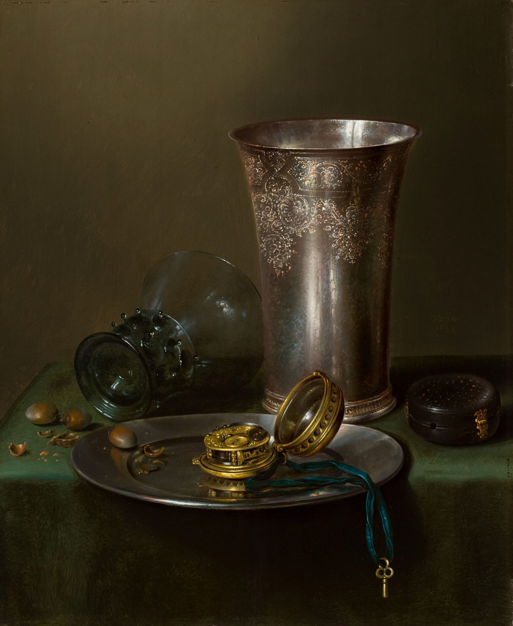 A still life with a silver goblet and a watch on a pewter plate